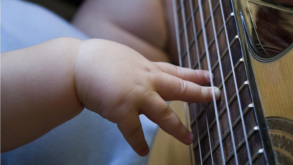 Baby plays guitar