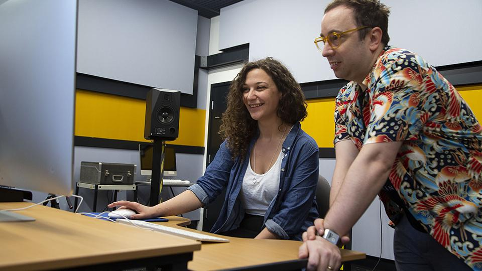 Lamis (Ell) Harper and Paul Sandell from EMIPM look at a computer in the music studios