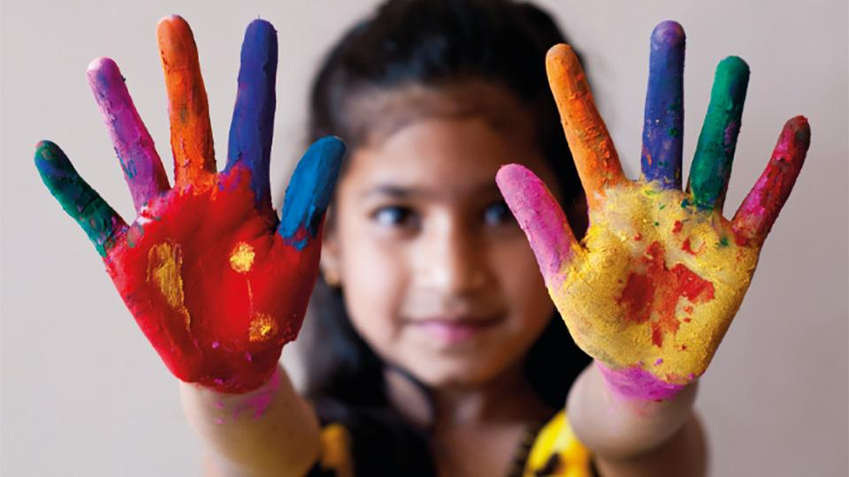 A young girl with rainbow paint on the palms of her hands
