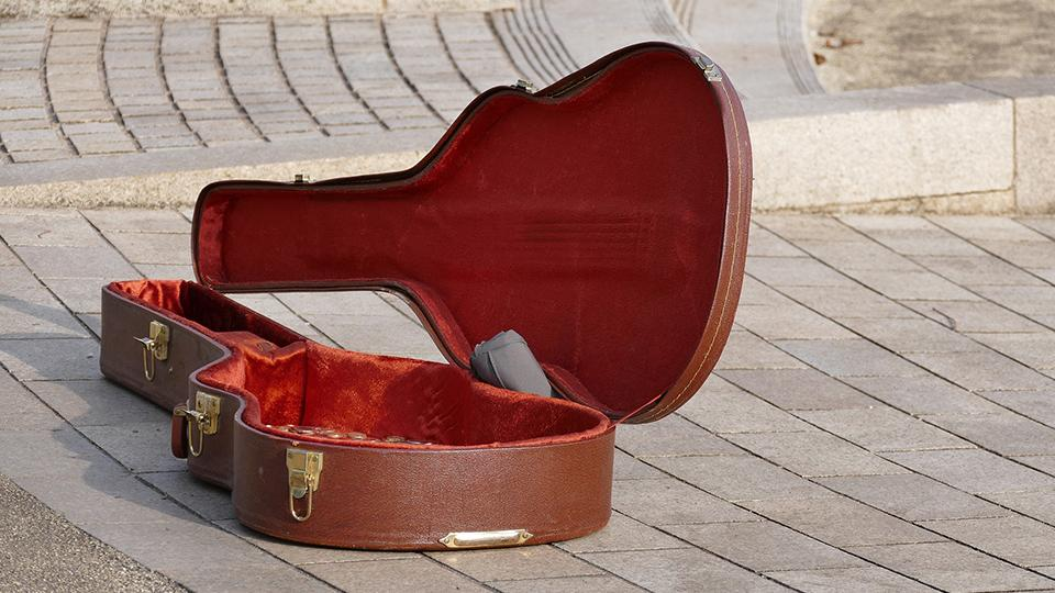 A picture of a busker's guitar lying on the ground