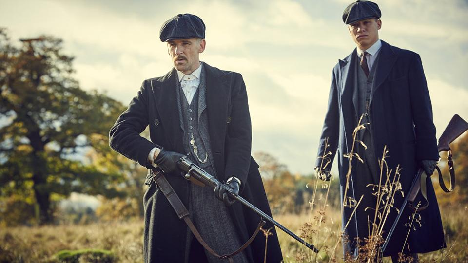 Image of Peaky Blinders characters Arthur Shelby and Michael Gray in a field, dressed in grey suits and coats, carrying shotguns