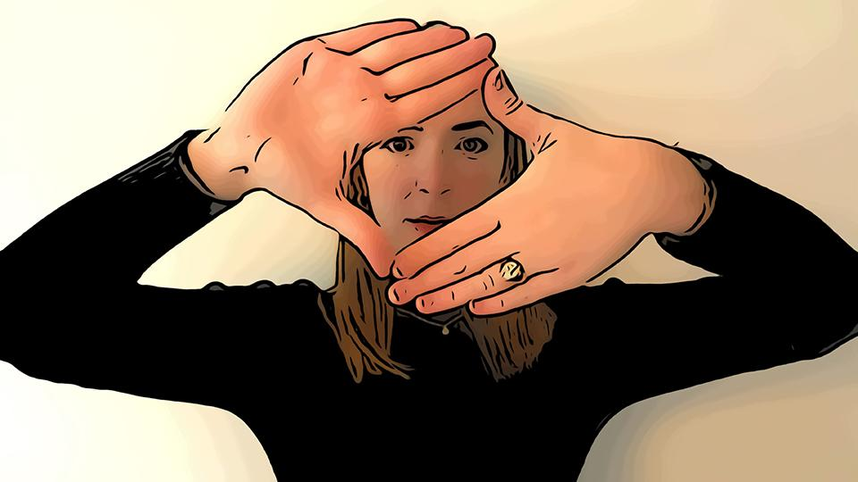 Image shows a woman with hands positioned in front of her face to form a diamond shape