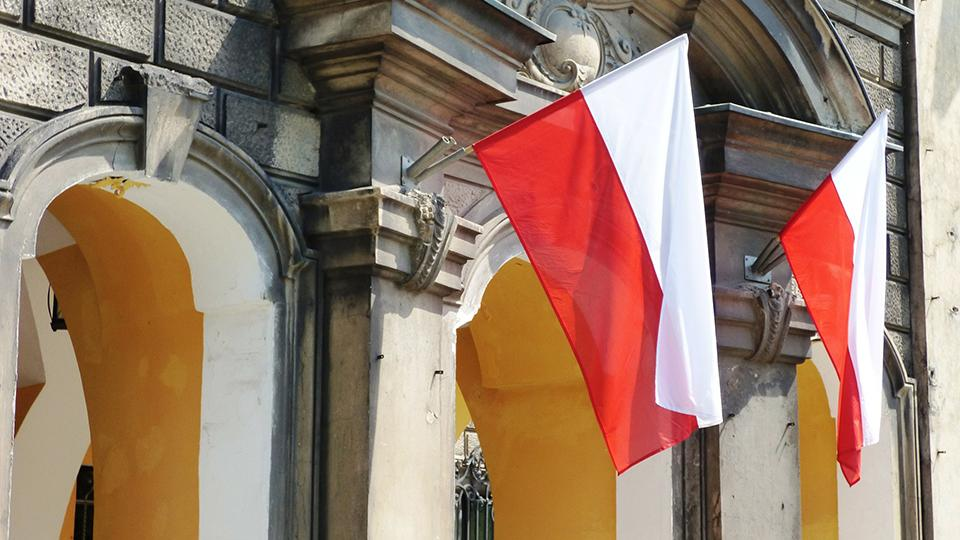 Two red and white Polish flags hang from a building