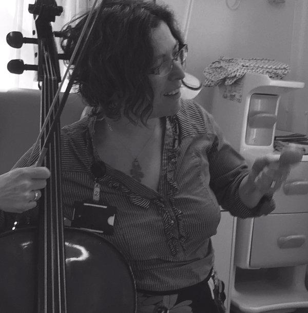 Course Tutor Bela Emerson in Black and White photograph playing cello