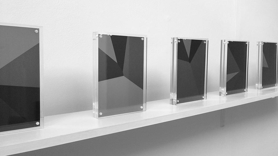 Black and white photograph of a shelf with a row of perspex frames with geometric, greyscale graphic images.