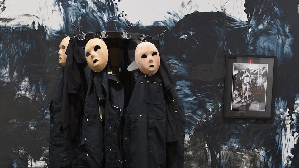 Large coat-stand with black overalls and masks in front of a roughly painted black wall.