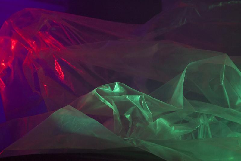 Crumpled plastic sheet lit red and green on dark background