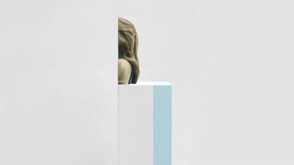 Sliced figurative sculpture on white plinth with vertical blue stripe in centre of white-walled space