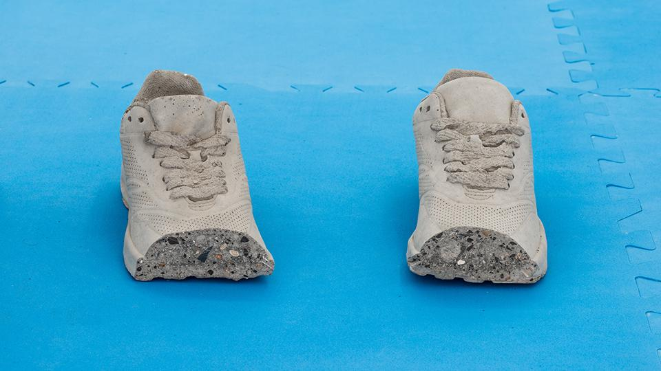 Concrete cast of a pair of trainers with the toes missing
