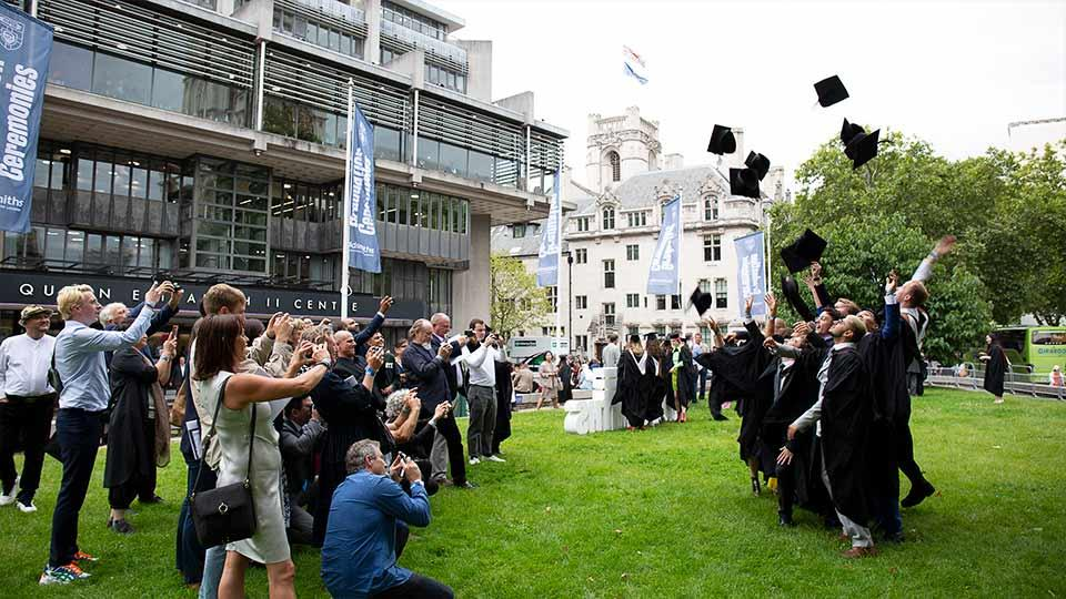 Graduates throw their hats in the air outside the QEII Centre