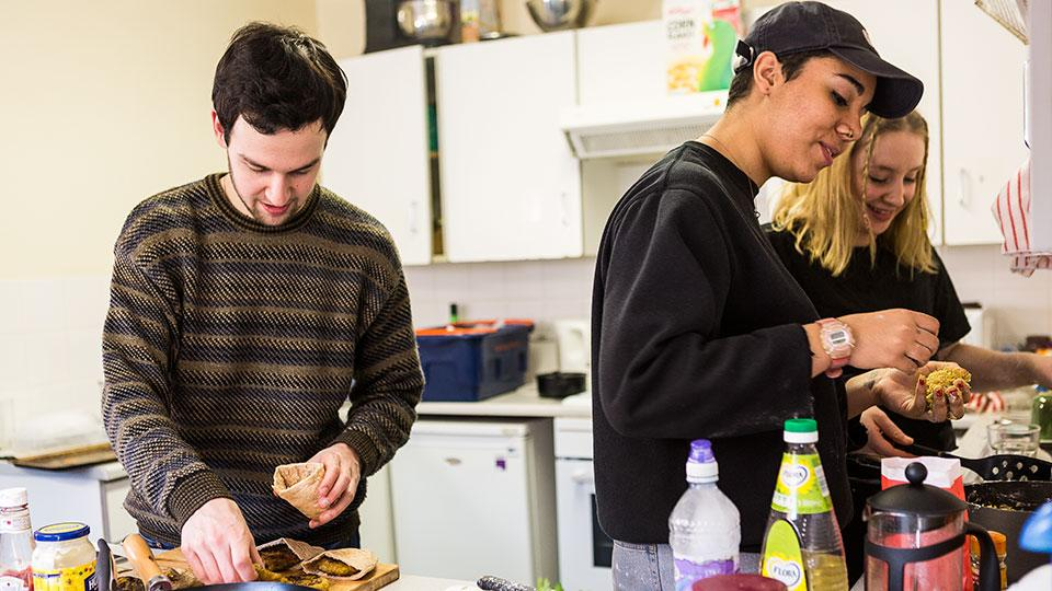 Flatmates cooking together in Loring Hall kitchen