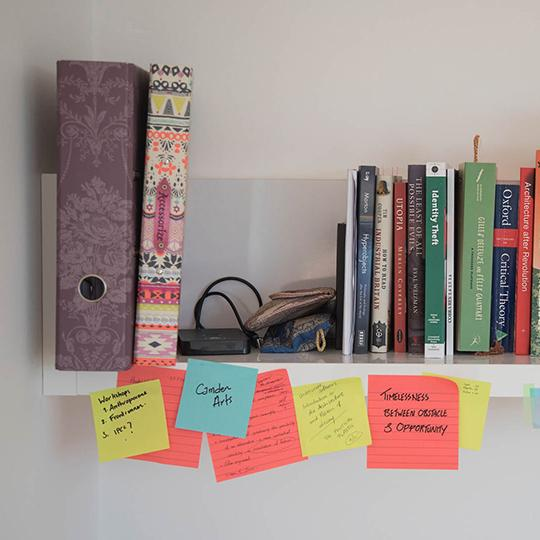 A student's bookcase on a white wall with brightly coloured folders and books and post-its hanging off it.