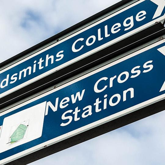 Closeup of a sign for New Cross station.