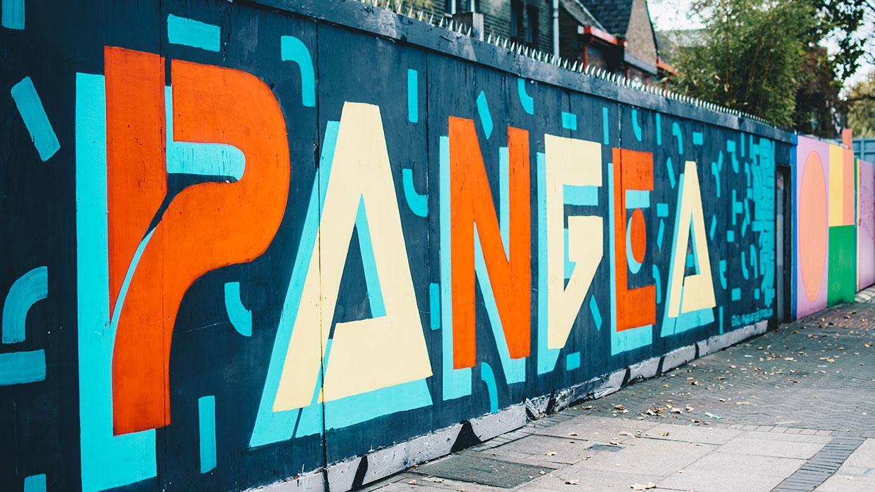Graffiti made up of orange and yellow letters on a blue wall spelling out 'pangea'