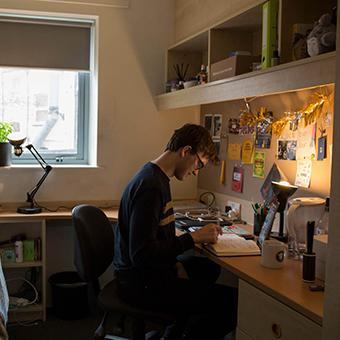 A male student sitting at his desk in his university room